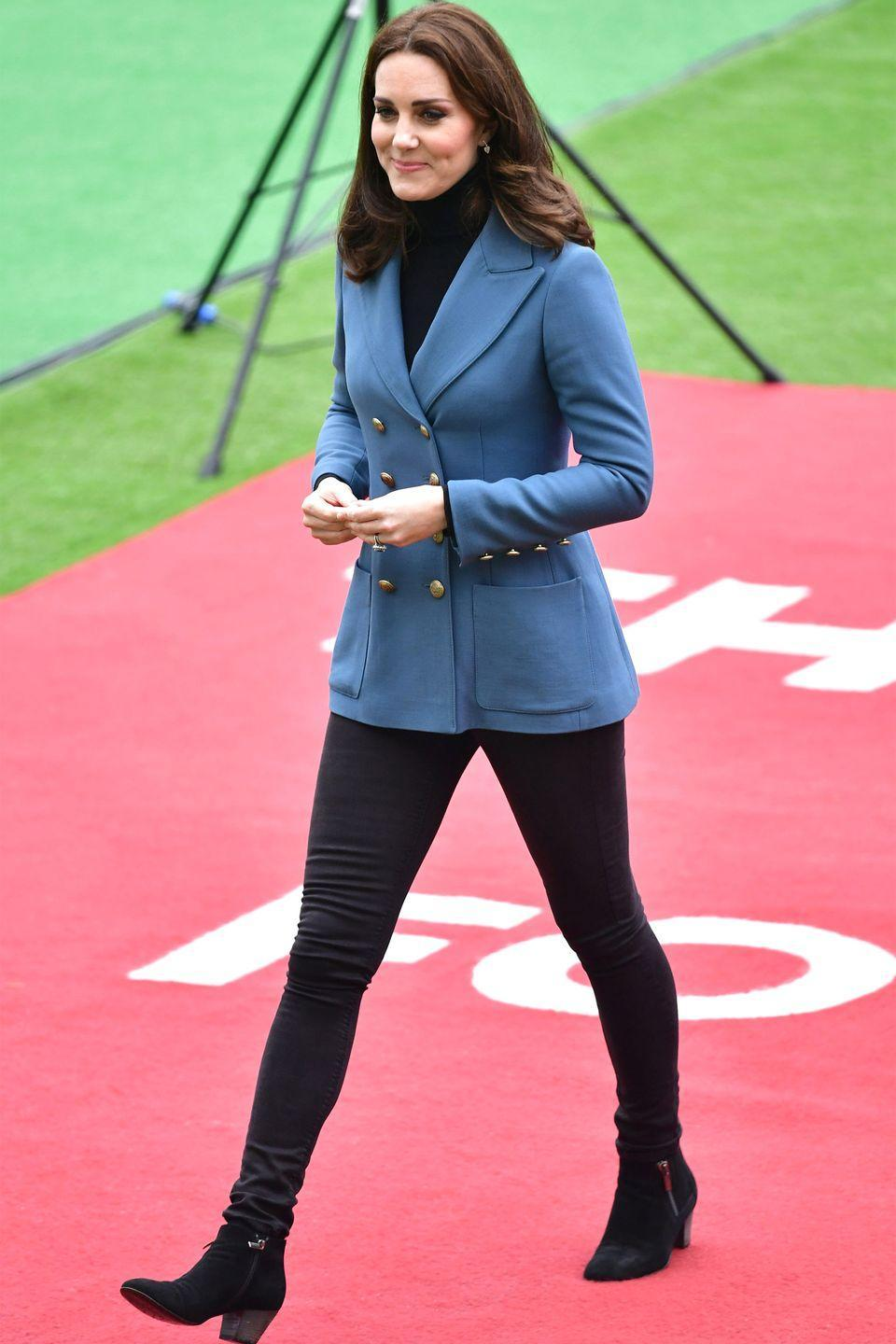 <p>The Duchess wears a double breasted blazer by Philosophy di Lorenzo Serafini, black jeans, suede ankle boots, a black turtleneck, and Kiki McDonough earrings at the London Stadium for a Coach Core graduation ceremony.</p>
