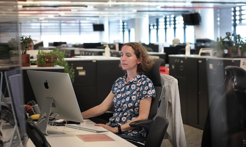 Suzanne Warr at her desk, looking at a Mac