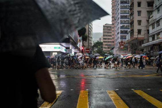 Under heavy rain, Gigi walks to join other protesters in their march through Wan Chai (Nicole Tung/Washington Post)