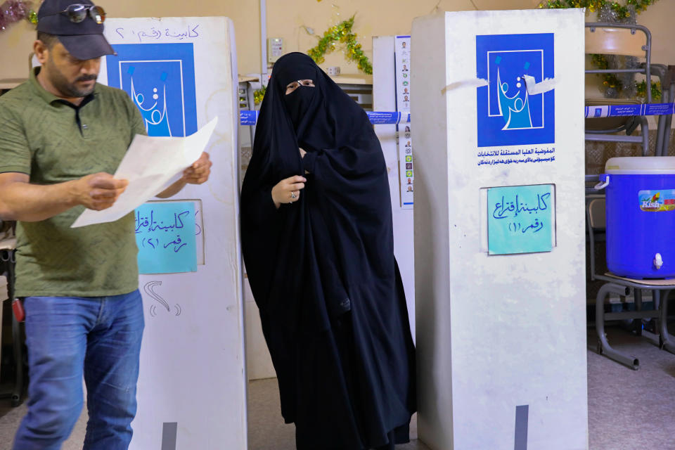 People cast their votes during the parliamentary elections in Basra, Iraq, Sunday, Oct. 10, 2021. Iraq closed its airspace and land border crossings on Sunday as voters headed to the polls to elect a parliament that many hope will deliver much needed reforms after decades of conflict and mismanagement. (AP Photo/Nabil al-Jurani)