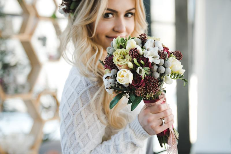 Portrait of Beautiful young bride in white wedding knitted dress with nice bouquet of flowers