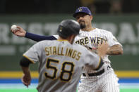 Milwaukee Brewers' Jace Peterson throws to first base to turn a double play after tagging out Pittsburgh Pirates' Jacob Stallings (58) at second base during the fourth inning of a baseball game Saturday, April 17, 2021, in Milwaukee. (AP Photo/Aaron Gash)