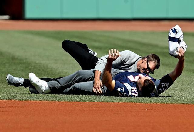 Rob Gronkowski is tackled by Tom Brady after stealing his jersey before Monday's opening day game between the Red Sox and Pirates at Fenway Park. (Getty Images)
