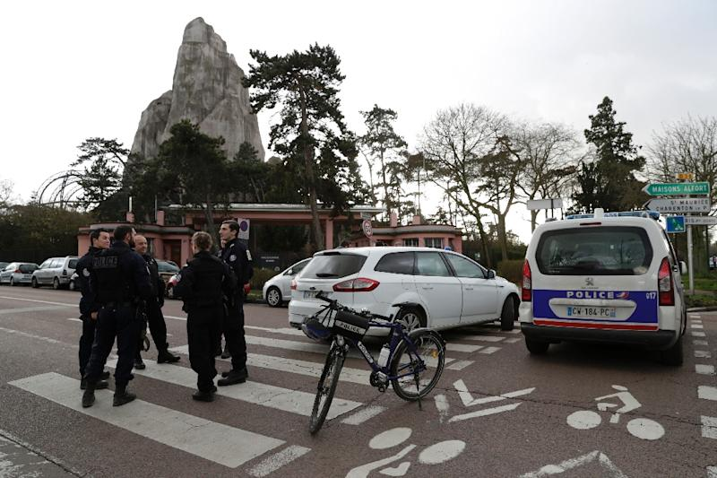 "Police officers outside Paris's main zoo, with the ""grand rocher"", where three baboons remain, visible in the background (AFP Photo/Thomas SAMSON)"