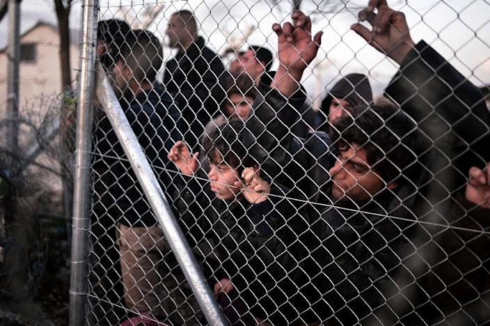 Refugees look through a fence towards the Macedonian side at the Greek-Macedonian border near the village of Idomeni on March 1, 2016 (AFP Photo/Louisa Gouliamaki)
