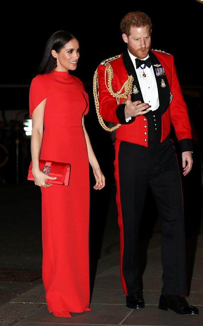 <p>A coordinating couple! Meghan Markle paired a fiery cape dress, shoes, and handbag to perfectly complement Prince Harry's uniform.</p>