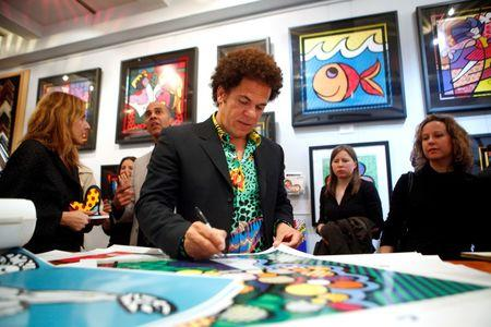 Artist Romero Britto signs posters at a gallery in New York