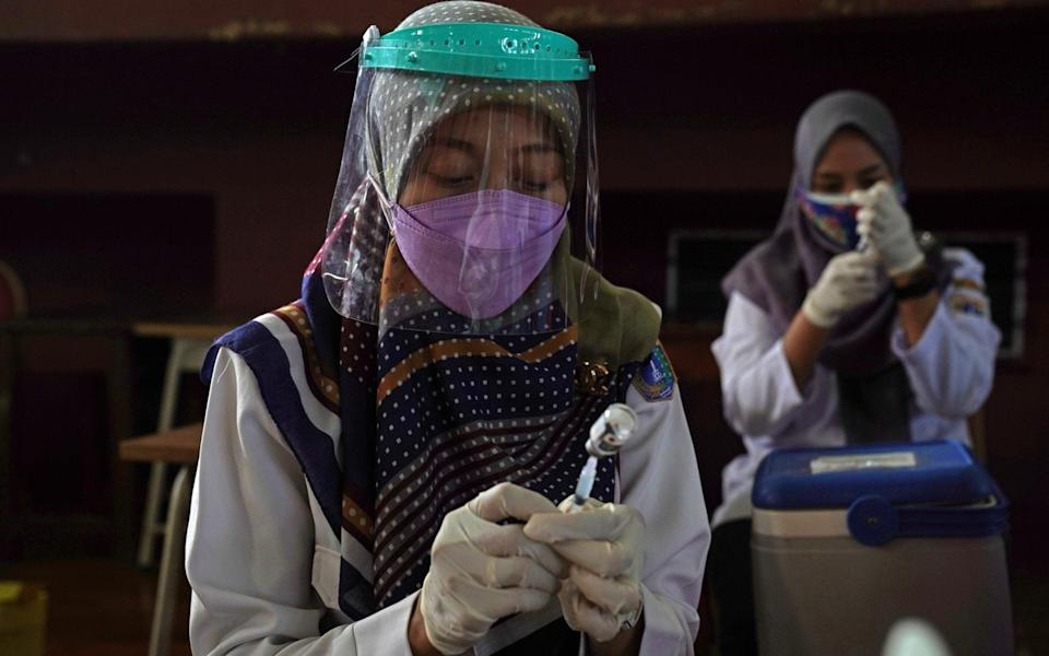 In Jakarta, Indonesia, health workers prepare doses of the Sinovac Biotech Ltd. Covid-19 vaccine at a vaccination centre - Dimas Ardian/Bloomberg