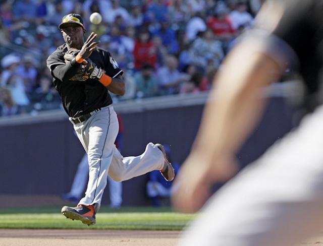 Miami Marlins shortstop Adeiny Hechavarria throws out Chicago Cubs' Starlin Castro at first base during the seventh inning of a baseball game in Chicago, Friday, June 6, 2014. (AP Photo/Nam Y. Huh)