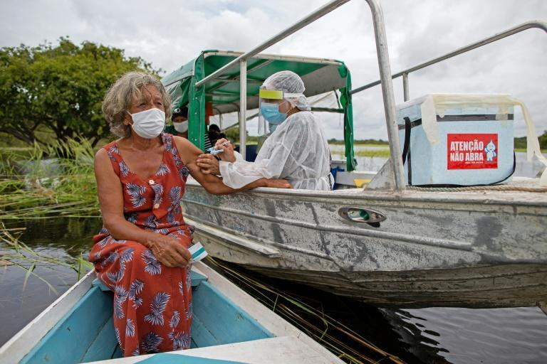Olga D'arc Pimentel, 72, is vaccinated by a health worker with a dose of Oxford-AstraZeneca COVID-19 vaccine ty on the banks of the Rio Negro near Manaus, Amazonas state, Brazil