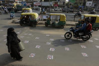 An Indian Muslim woman walks as commuters move on defaced images of French President Emmanuel Macron pasted by protestors on a road in Ahmedabad, India, Sunday, Nov. 1, 2020. Muslims have been calling for both protests and a boycott of French goods in response to France's stance on caricatures of Islam's most revered prophet. (AP Photo/Ajit Solanki)