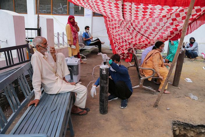 """COVID-19 patients receive oxygen outside a government run hospital in Jammu, India, on May 12, 2021.<span class=""""copyright"""">Channi Anand—AP</span>"""