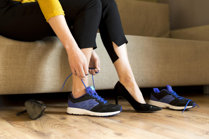 A woman lacing up a sneaker on her right foot while wearing a high heel on her left foot.