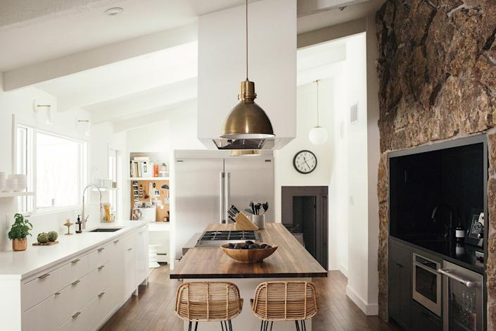 """<div class=""""caption""""> <strong>AFTER</strong>: Using 3D modeling, Laura and Scott were able to determine that the hood looked best at the center of the room, surrounded by a walnut island and quartz countertops. Pairs of <a href=""""https://fave.co/3l7UXvB"""" rel=""""nofollow noopener"""" target=""""_blank"""" data-ylk=""""slk:Crate and Barrel pendants"""" class=""""link rapid-noclick-resp"""">Crate and Barrel pendants</a> and <a href=""""https://asherandrye.com/collections/dining-chairs-stools/products/rattan-counter-stool-natural"""" rel=""""nofollow noopener"""" target=""""_blank"""" data-ylk=""""slk:Asher + Rye counter stools"""" class=""""link rapid-noclick-resp"""">Asher + Rye counter stools</a> complete the look. </div> <cite class=""""credit"""">Davin Lindwall</cite>"""