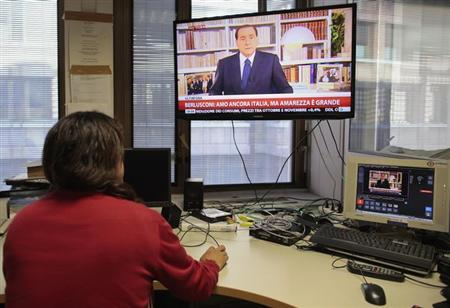 A journalist watches footage of Italy's former Prime Minister Silvio Berlusconi's pre-recorded nationwide television address, in Rome September 18, 2013.