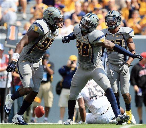 West Virginia cornerback Terence Garvin (28) celebrates a tackle on Maryland's Brandon Ross (45) with teammates Will Clarke (98) and Brodrick Jenkins (23) during the first half of an NCAA college football game in Morgantown, W.Va., Saturday, Sept. 22, 2012. (AP Photo/Christopher Jackson)
