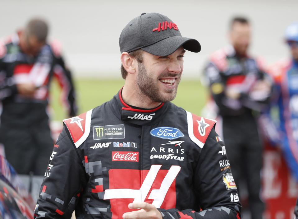 FILE - Daniel Suarez stands next to his car before a NASCAR cup series auto race at Michigan International Speedway in Brooklyn, Mich. in this Monday, June 10, 2019, file photo. New NASCAR team Trackhouse Racing has brought entertainer Pitbull on as an ownership partner for an organization making its debut next month at the Daytona 500. Trackhouse was launched late last year by former driver Justin Marks. The team has hired driver Daniel Suarez. It will not be NASCAR's first pairing of a Hispanic driver and team owner. (AP Photo/Carlos Osorio, File)