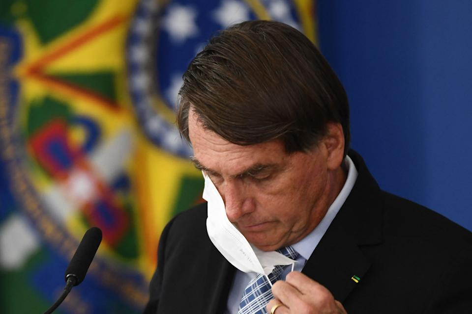 Brazilian President Jair Bolsonaro takes off his face mask before speaking during the sanction of the law that authorizes states, municipalities and the private sector to buy vaccines against COVID-19, at the Planalto Palace in Brasilia, on March 10, 2021. - Until now, with more than 260,000 deaths by the coronavirus, only the federal Government was authorized to buy vaccines. (Photo by EVARISTO SA / AFP) (Photo by EVARISTO SA/AFP via Getty Images)