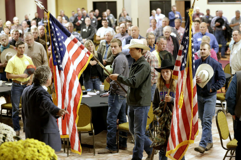 American flags are carried in at the start of a meeting and rally in Omaha, Neb., Wednesday, Oct. 2, 2019, to urge President Trump and U.S. Department of Agriculture Secretary Perdue to ensure fair prices for cattle farmers and ranchers. Among items on the agenda is a call to withdraw from the United States Mexico Canada Agreement (USMCA) until such time as Country of Origin Labeling (COOL) is included in the language of the agreement, and to reduce the amount of foreign beef imported into the United States and cease all efforts to reopen the U.S. to Brazilian beef. (AP Photo/Nati Harnik)