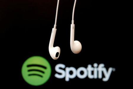 Headphones are seen in front of a logo of online music streaming service Spotify in this  February 18, 2014 illustration picture. REUTERS/Christian Hartmann/File Photo