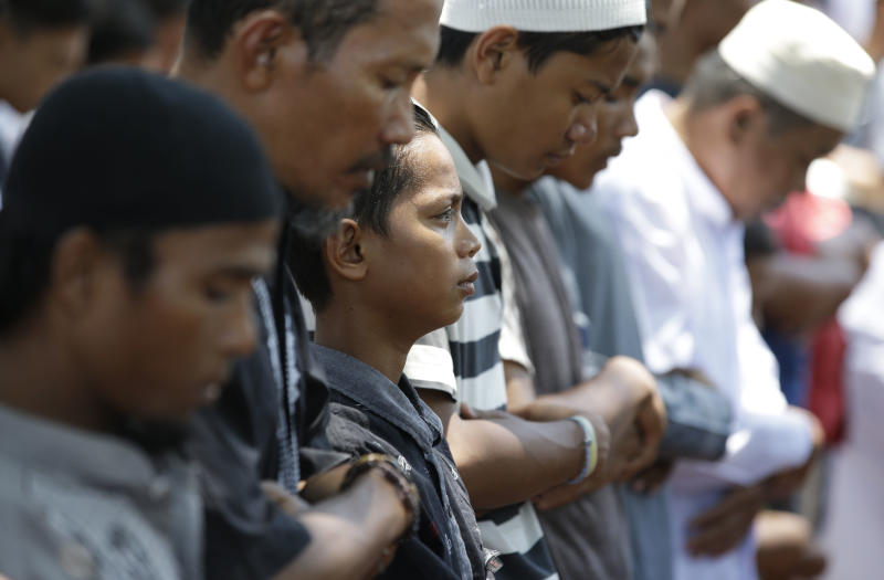 A boy is teary-eyed as he joins during Friday prayers outside a damaged mosque caused by the massive earthquake and tsunami in Palu, Central Sulawesi, Indonesia Oct. 5, 2018. French rescuers say they've been unable to find the possible sign of life they detected a day earlier under the rubble of a hotel that collapsed in the earthquake a week ago on Indonesia's Sulawesi island. (AP Photo/Aaron Favila)