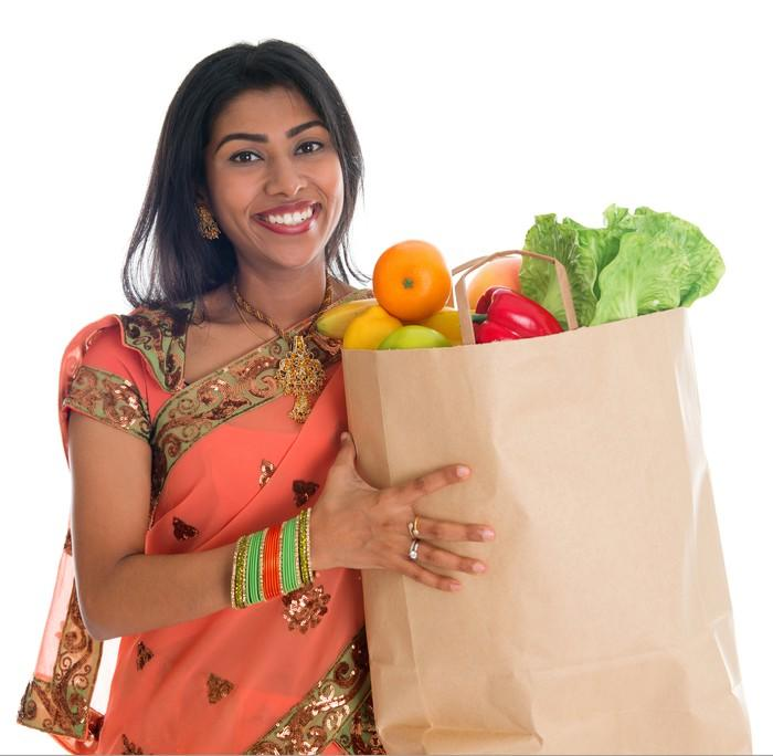 A woman from India holds a grocery bag. Getty image