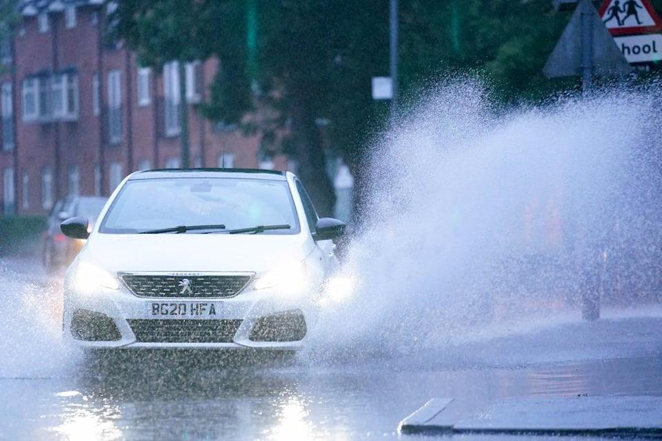 Cars drive through standing water after heavy overnight rain showers in Warwick, Warwickshire (Jacob King/PA) (PA Wire)