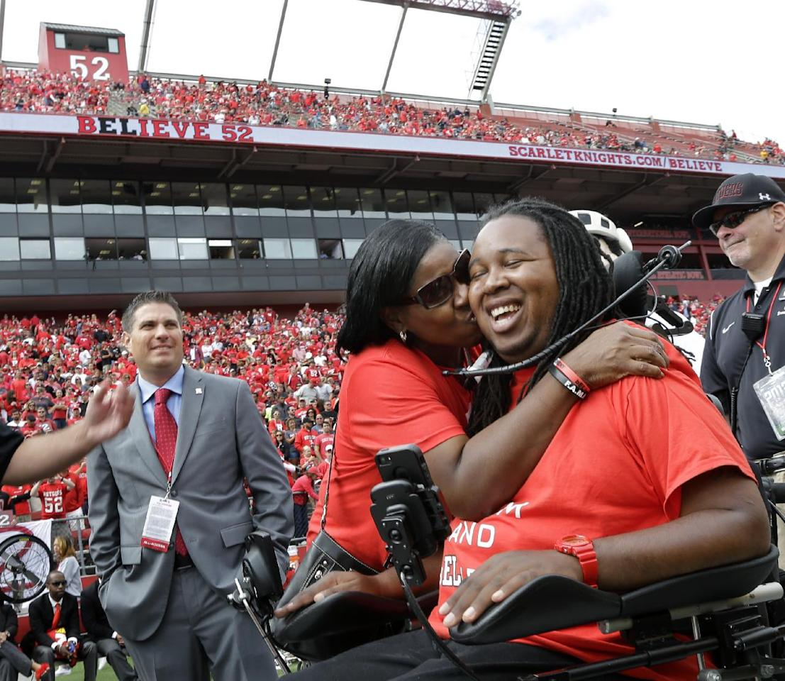 Former Rutgers football player Eric LeGrand is kissed by his mother Karen during ceremony where his jersey No. 52 was retired at halftime of an NCAA college football game against Eastern Michigan in Piscataway,N.J., Saturday, Sept. 14, 2013. LeGrand became paralyzed while making a tackle in an October 2010 game. (AP Photo/Mel Evans)