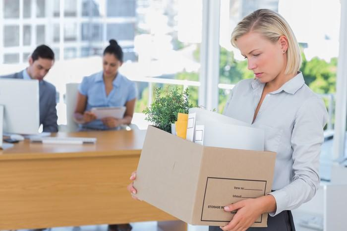 Woman holding box of office supplies, looking down, with two people sitting at a desk in the background.
