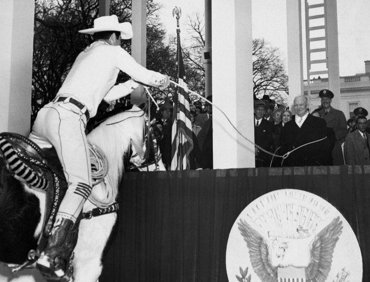 Dwight D. Eisenhower, center, seems to be getting a big kick out of being lassoed by Monte Montana. (AP Photo)