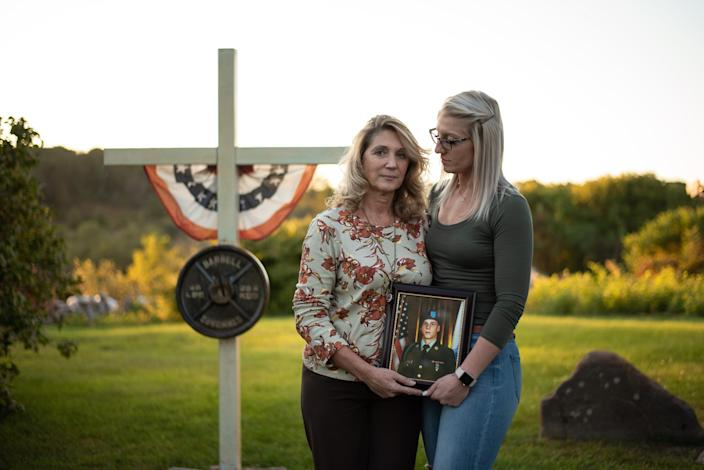 Jill Richardson Perez and her daughter, Ashleigh Coons, stand in front of a cross in Perez's front yard in Broadalbin, New York on Wednesday, Sept. 18, 2019. Perez's son Matthew Coons was one of 20 people killed in a limousine crash in Schoharie, New York on Oct. 6, 2018.