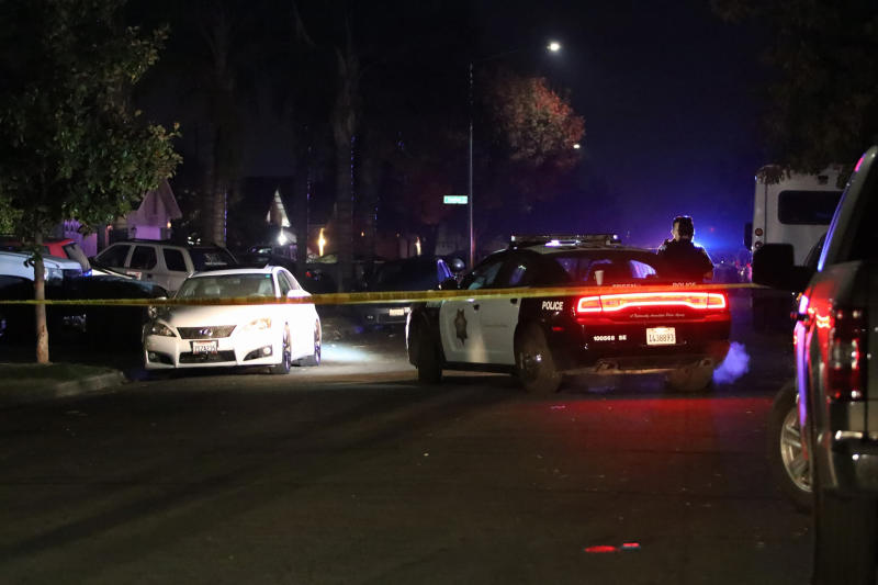 Police work at the scene of a shooting, Sunday, Nov. 17, 2019, in southeast Fresno, Calif. Multiple people were shot and at least four of them were killed Sunday at a party in Fresno when suspects sneaked into the backyard and fired into the crowd, police said. (Larry Valenzuela/The Fresno Bee via AP)