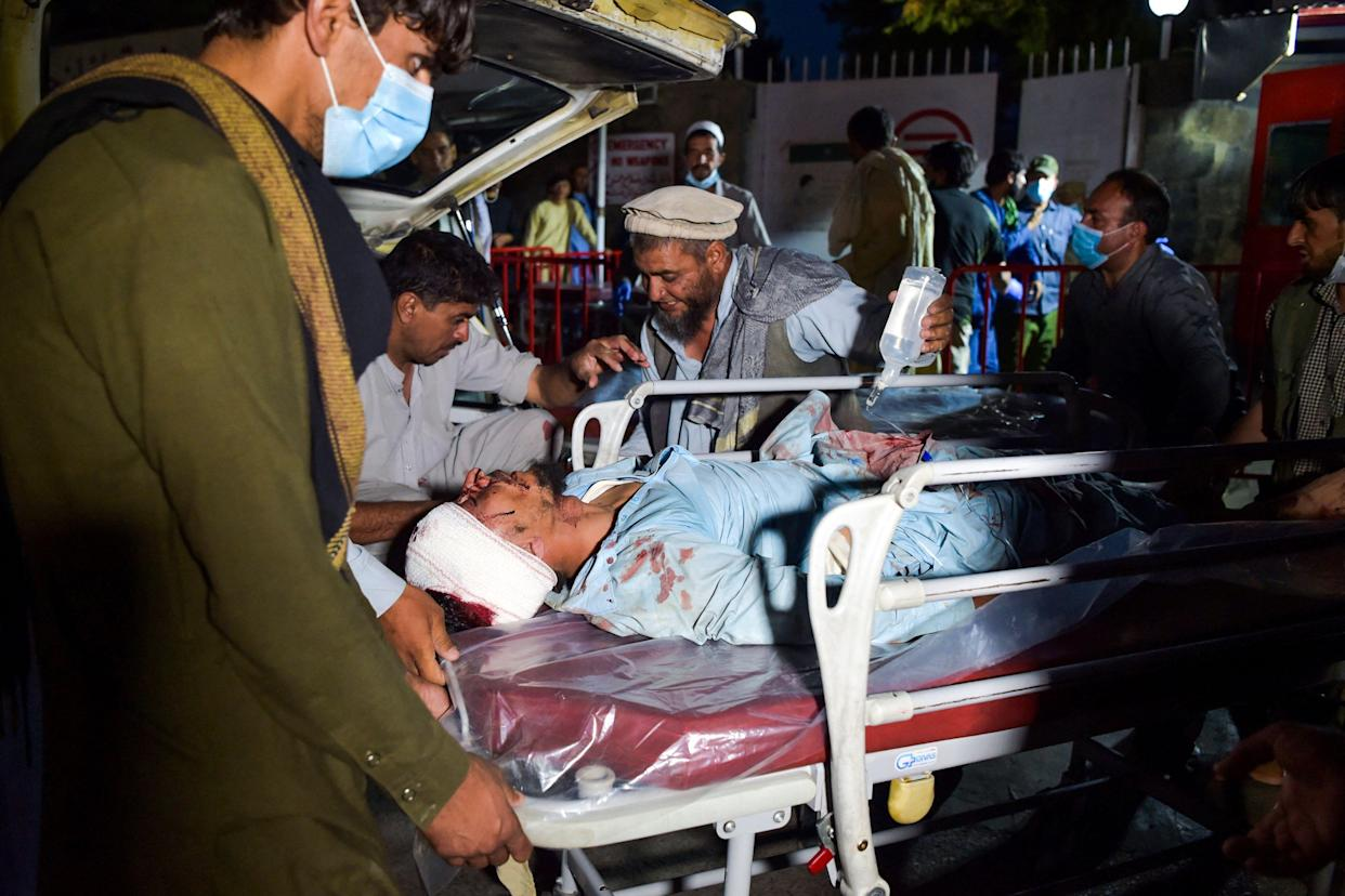 Medical and hospital staff bring an injured man on a stretcher for treatment