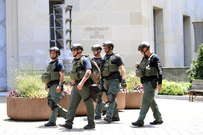 Officers walk outside the Department of Justice as Attorney General William Barr speaks during a virtual press conference inside the building Thursday, June 4, 2020, in Washington. (AP Photo/Manuel Balce Ceneta)