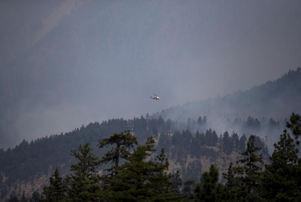 A helicopter pilot prepares to drop water on a wildfire burning in Lytton, British Columbia, Friday, July 2, 2021. Officials on Friday hunted for any missing residents of the British Columbia town destroyed by wildfire as Canadian Prime Minister Justin Trudeau offered federal assistance. (Darryl Dyck/The Canadian Press via AP)