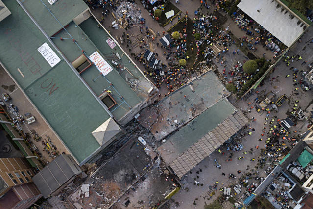 <p>Volunteers and rescue workers search for children trapped inside the Enrique Rebsamen school, collapsed by a 7.1 earthquake in southern Mexico City, Sept. 20, 2017. (Photo: Miguel Tovar/AP) </p>