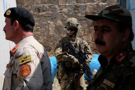 A soldier with the British army's Royal Irish Regiment provides security for a meeting between international military advisers and Afghan officials at a base in Kabul