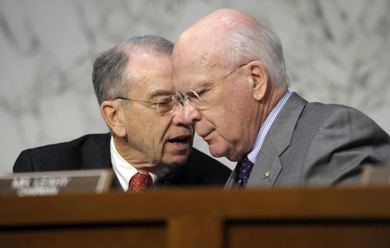 Senate Judiciary Committee Chairman Sen. Patrick Leahy, D-Vt., right, talks with the committee's ranking Republican Sen. Charles Grassley, R-Iowa, on Capitol Hill in Washington, Wednesday, Feb. 13, 2013, during the committee's hearing on comprehensive immigration reform. (AP Photo/Susan Walsh)
