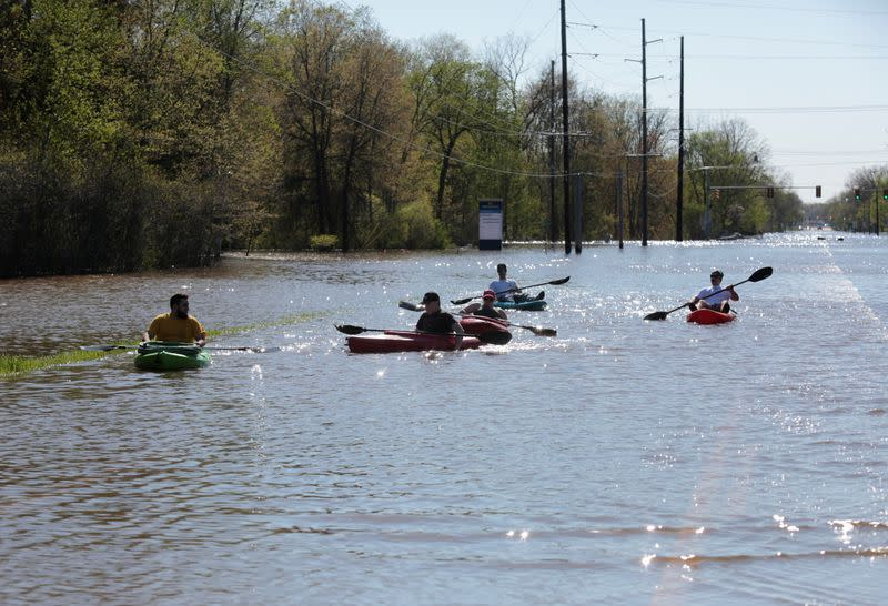 Residents paddle kayaks along a flooded street along the Tittabawassee River, after two dam failures submerged parts of Midland, Michigan