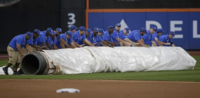 Groundskeepers roll the tarp onto the outfield as rain headed into the area after the first inning of a baseball game between the Washington Nationals and the New York Mets Thursday, Sept. 12, 2013, in New York. (AP Photo/Kathy Willens)