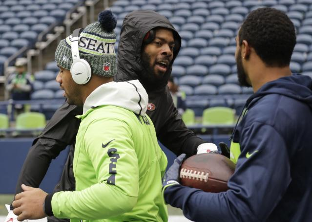 San Francisco 49ers cornerback Richard Sherman, center, greets Seattle Seahawks quarterback Russell Wilson, left, and wide receiver Doug Baldwin, right, during warmups before an NFL football game, Sunday, Dec. 2, 2018, in Seattle. (AP Photo/Elaine Thompson)
