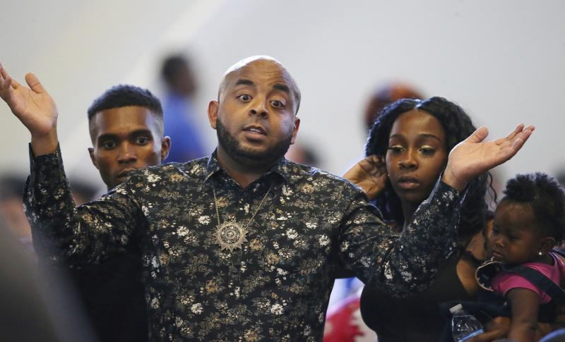 FILE - In this June 18, 2019, file photo, Rev. Jarrett Maupin, front, gestures in frustration as he arrives with Dravon Ames, left, Lesha Harper, second from right, and one of the family's two daughters, 1-year-old London, right, prior to the start of a community meeting in Phoenix. The community meeting stemmed from reaction to a videotaped encounter that surfaced recently of Ames and his pregnant fiancee, Harper, having had guns aimed at them by Phoenix police during a response to a shoplifting report, as well as the issue of recent police-involved shootings in the community. The Phoenix Police Department says it will train officers to track when they point their guns at people. The department announced Friday, Aug. 2 the policy was recommended by the Community Police Trust Initiative and the National Police Foundation, which studied last year's police shootings in the city. The policy will go into effect Aug. 19. (AP Photo/Ross D. Franklin, File)