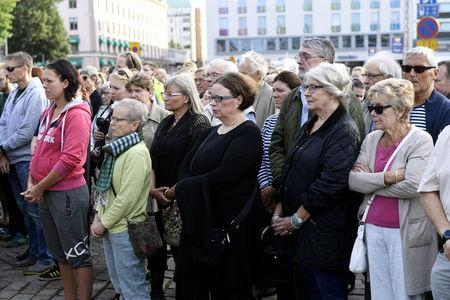People attend a moment of silence to commemorate the victims of Friday's stabbings at the Turku Market Square in Turku, Finland August 20, 2017. Lehtikuva/Vesa Moilanen via REUTERS       ATTENTION EDITORS - THIS IMAGE WAS PROVIDED BY A THIRD PARTY. NO THIRD PARTY SALES. NOT FOR USE BY REUTERS THIRD PARTY DISTRIBUTORS. FINLAND OUT. NO COMMERCIAL OR EDITORIAL SALES IN FINLAND.