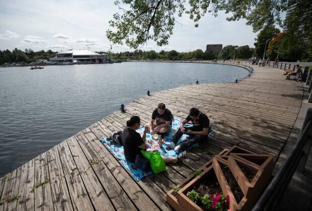 A family picnics on the boardwalk at Dows Lake. While many traditional spring break activities are on hold this year, there still are countless options — as long as you use a bit of creativity. (Justin Tang/Canadian Press - image credit)