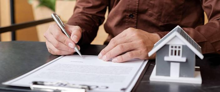 Close up of man signing contract for homeowners insurance.