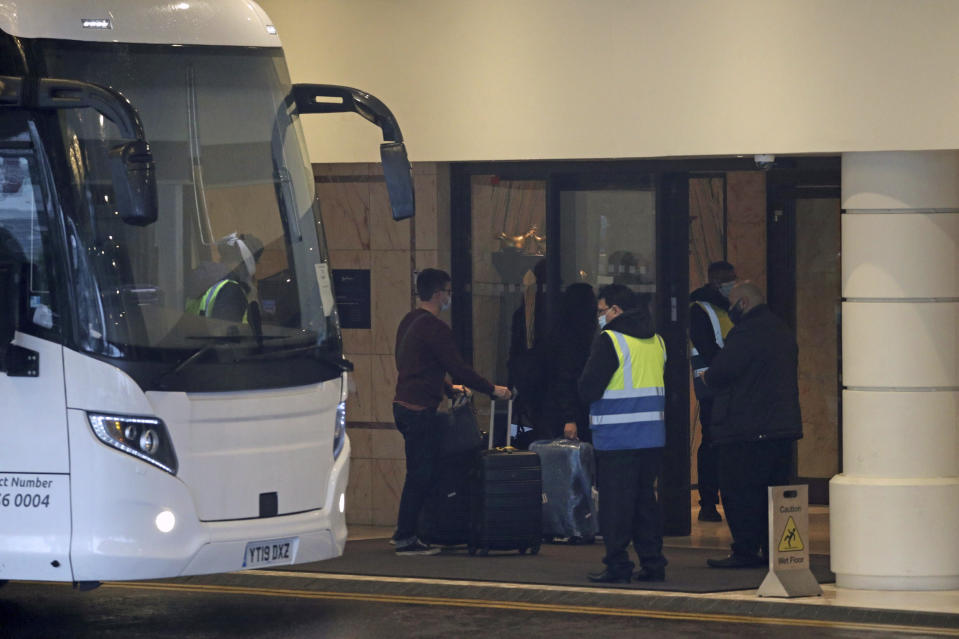 """A coach delivers passengers to the Radisson Blu Edwardian Hotel, near Heathrow Airport, London, Monday Feb. 15, 2021 where they will remain during a 10 day quarantine period after returning to England from one of 33 """"red list"""" countries. New regulations now in force require anyone who has been in a 'high-risk' location to enter England through a designated port and have pre-booked a package to stay at one of the Government's managed quarantine facilities. (Steve Parsons/PA via AP)"""