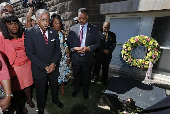 Rev. Julius Scruggs, second from left, leads people in prayer during a wreath laying ceremony at the 16th Street Baptist Church in Birmingham, Ala., Sunday, Sept. 15, 2013. The congregation gathered outside the church for the wreath laying ceremony at the spot where a bomb was detonated 50 years ago by the Ku Klux Klan, killing four young girls. Rev. Jesse Jackson is fourth from left. U.S. Rep. Terri Sewell, D-Ala., is at left. (AP Photo/Hal Yeager)