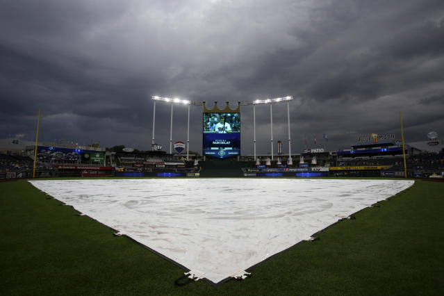 Storm clouds linger over Kauffman Stadium during a rain delay at a baseball game between the Kansas City Royals and the Toronto Blue Jays in Kansas City, Mo., Thursday, Aug. 16, 2018. (AP Photo/Colin E. Braley)