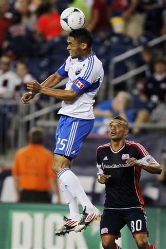Montreal Impact midfielder Lamar Neagle (25) makes contact with the ball as New England Revolution's Fernando Cardenas (80) watches during the second half of an MLS soccer match in Foxborough, Mass., Sunday, Aug. 12, 2012. Montreal won 1-0. (AP Photo/Steven Senne)