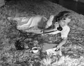 <p> The <em>To Be or Not to Be</em> actress lounges on shag carpeting with a cup of coffee during a telephone call at home in 1938. </p>